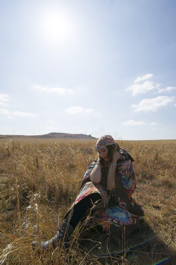 Brunette woman in tribal dress sitting in a field. royalty free stock photo