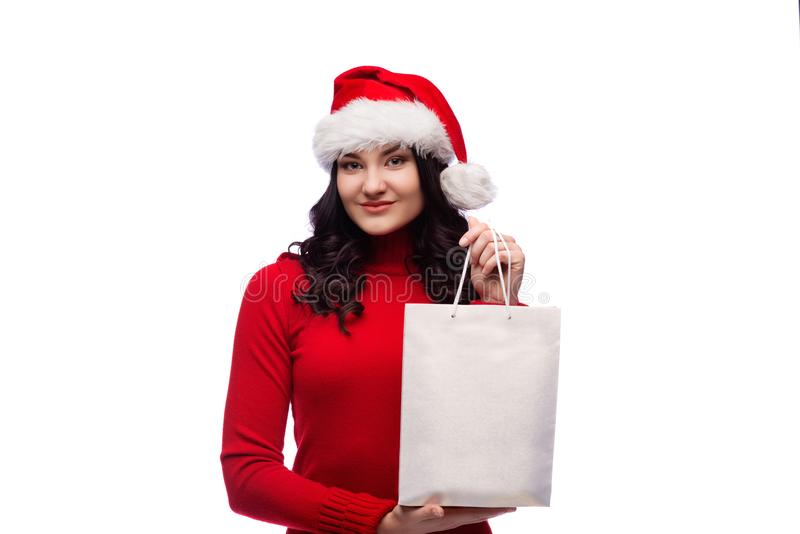 Brunette woman wearing christmas hat holding present with a happy face. Isolated stock image