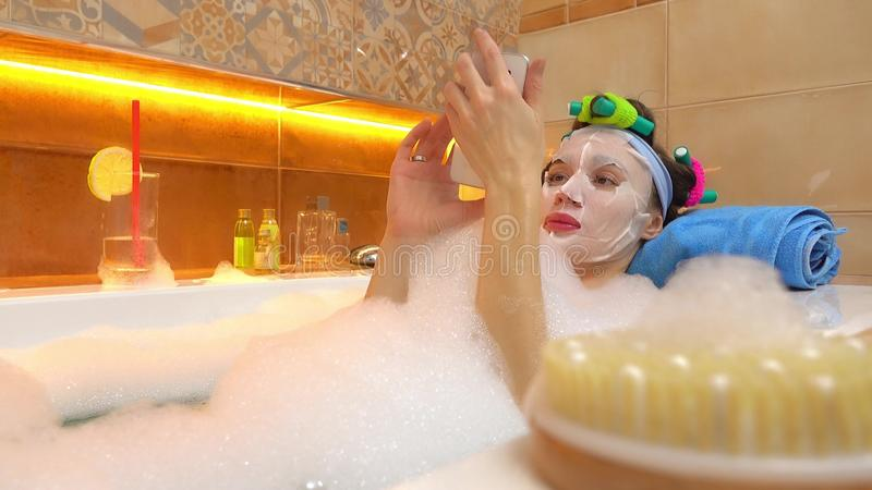 Brunette woman wearing face mask uses her mobile phone in foamy bathtub. Brunette woman wearing face mask uses her mobile phone in foamy bath stock photos