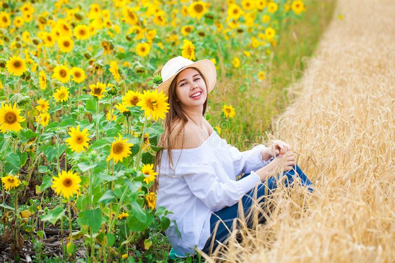 Brunette woman in white blouse sitting on a background of golden wheat and sunflowers fields royalty free stock images