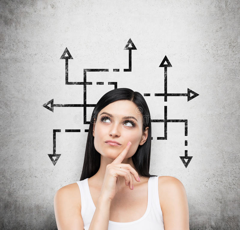 A brunette woman who is pondering about possible solutions of the complicated problem. Many arrows with different direct stock images
