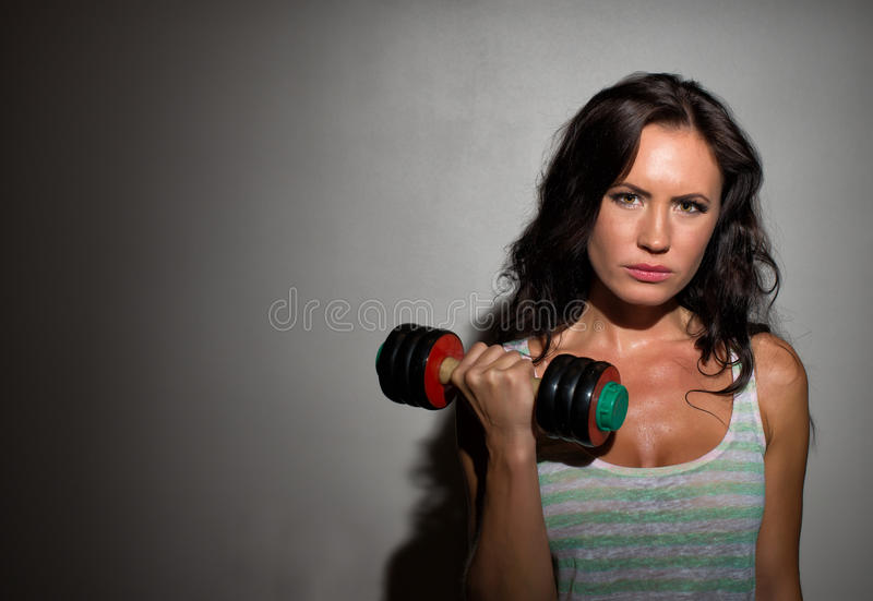 Brunette woman working out. Attractive brunette woman working out with dumbbells royalty free stock photography