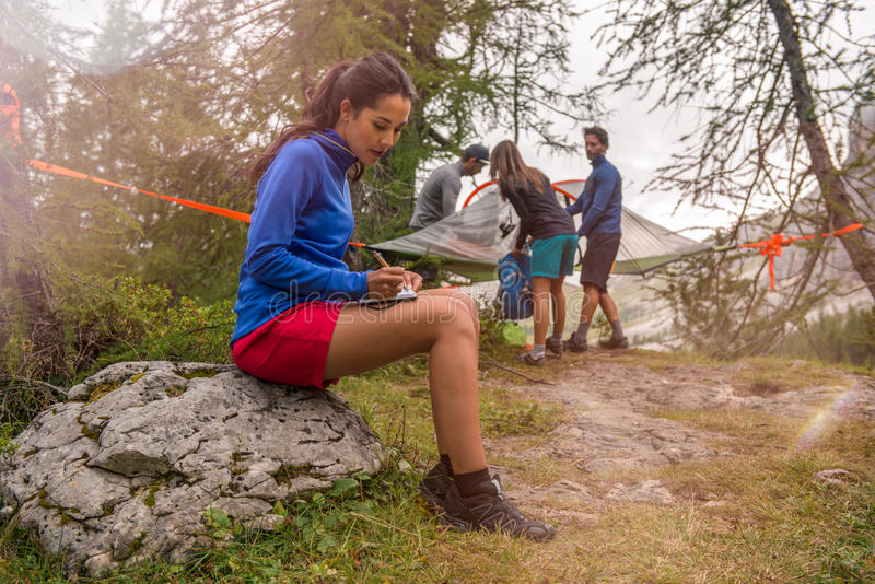 Brunette woman writing personal diary while friends setting hanging tent camping. Group of friends people summer. Brunette women writing personal diary while royalty free stock photos