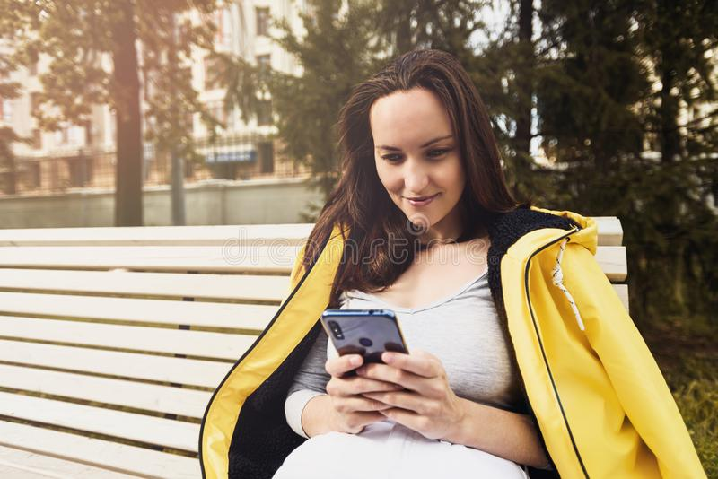 Woman in yellow jacket with smartphone in her hands sitting on bench royalty free stock photo