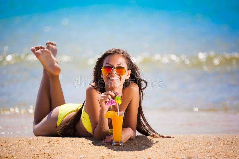 Brunette woman yellow swimsuit drink cocktail stock photography