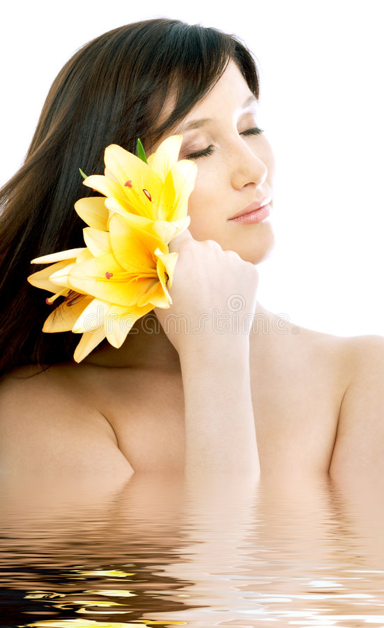 Brunette with yellow lily flowers in water. Topless brunette with yellow lily flowers in water stock photography