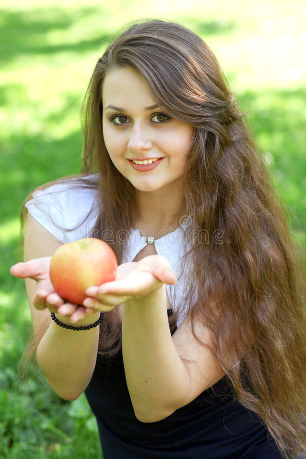 Brunette young girl with an apple royalty free stock photography