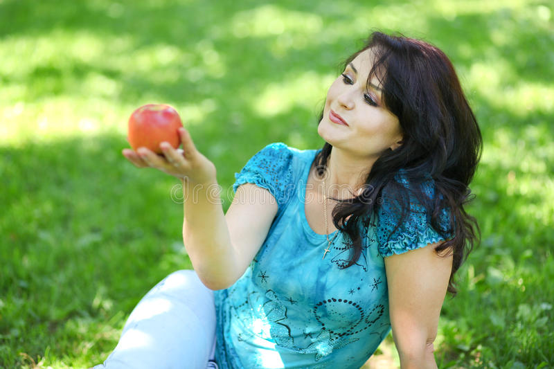 Brunette young girl with an apple stock photography
