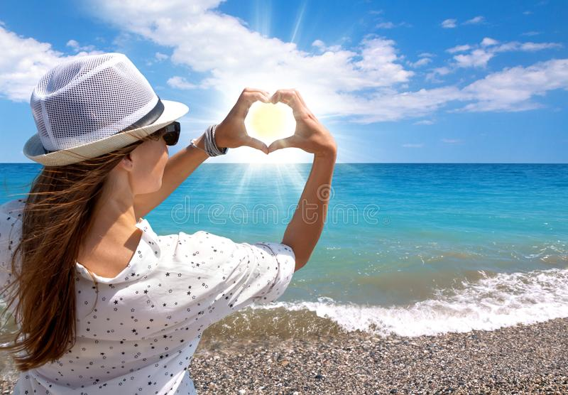 Brunette young girl holding hands in heart shape framing setting sun on sea beach stock images