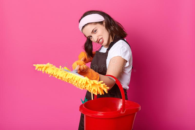 Brunette young housewife with directed yellow mop and red bucket. Brown apron. Happy woman works at home. Hardworking female royalty free stock image