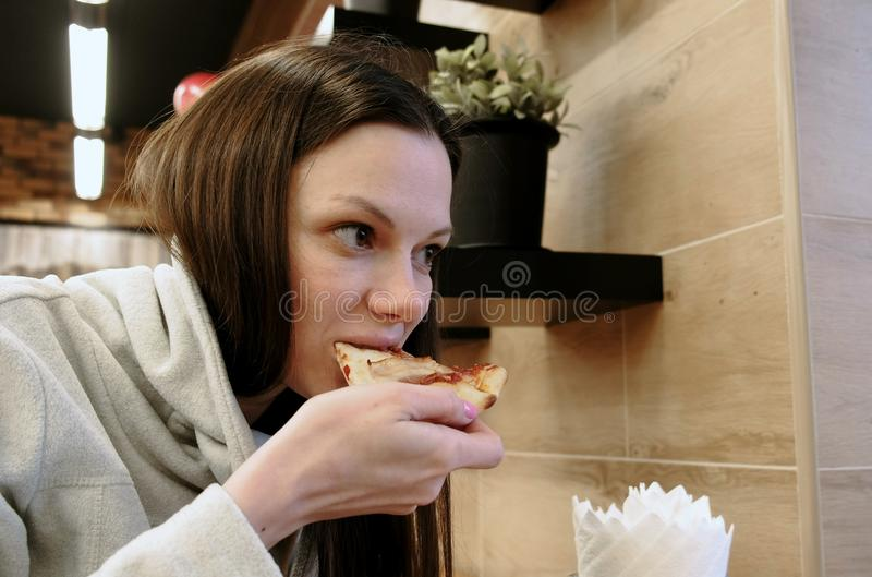 Brunette young hungry woman bites off a tasty slice of pizza and eat it, side view. stock photography