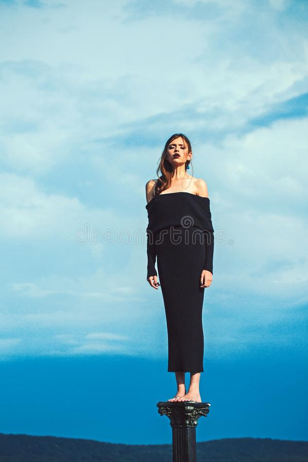 Brunette young woman in black dress. Girl posing on blue sky background. Girl. Fashion photo.  royalty free stock photography