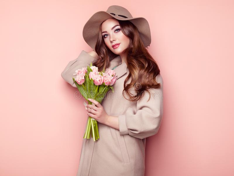 Brunette young woman in stylish greatcoat. And Hat. Girl in Beige Coat with Bouquet of Flowers. Model with Long Curly Hair. Spring Lookbook royalty free stock images