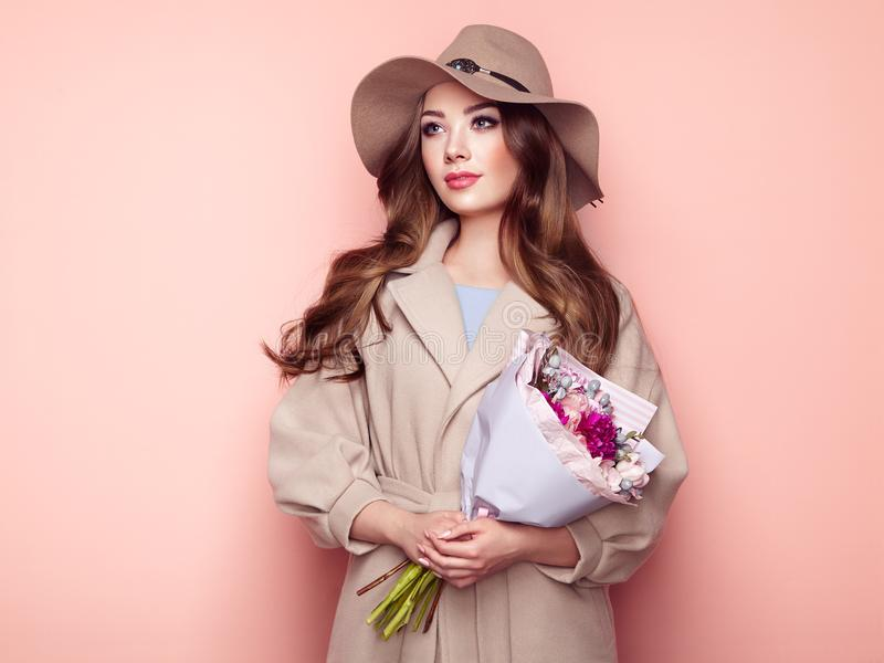 Brunette young woman in stylish greatcoat. And Hat. Girl in Beige Coat with Bouquet of Flowers. Model with Long Curly Hair. Spring Lookbook royalty free stock photography