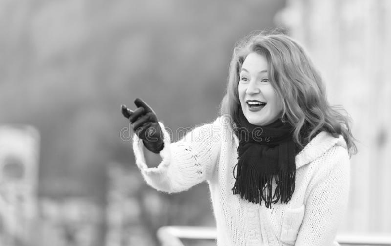 Attractive lady in white knitted coat and scurf. woman exited welcome on street. Brunette young woman in white knitted coat. Young attractive lady wiht black royalty free stock images