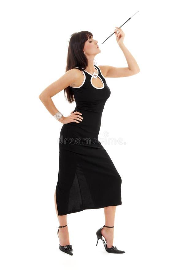 Brunette in zwarte kleding met sigarethouder stock fotografie