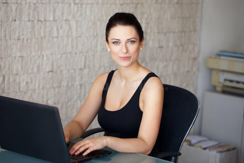Brunettebuchhalter, der auf Laptop im Büro schreibt stockbild
