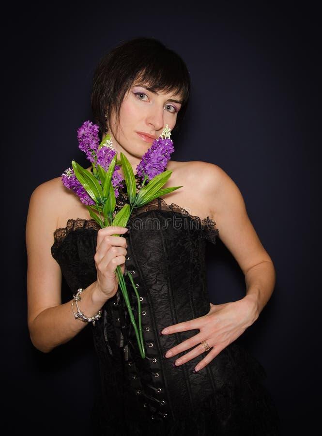 Brunettedame, die einen Blumenstrauß hält lizenzfreie stockfotografie