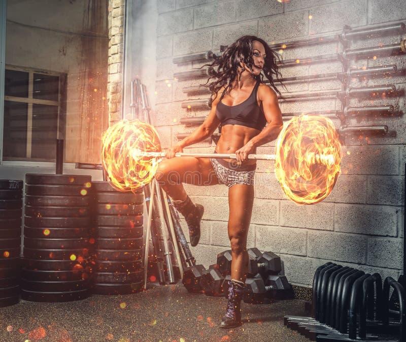 Brunetteeignungsfrau, die mit brennendem Barbell trainiert lizenzfreie stockfotografie