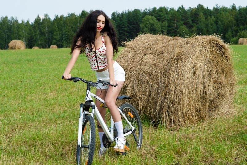 Brunettefrau auf Fahrrad auf dem Gebiet stockfotos