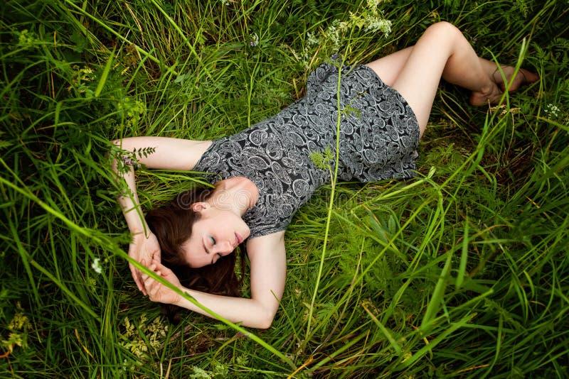 Brunettefrau, die auf grünem Gras liegt lizenzfreie stockbilder