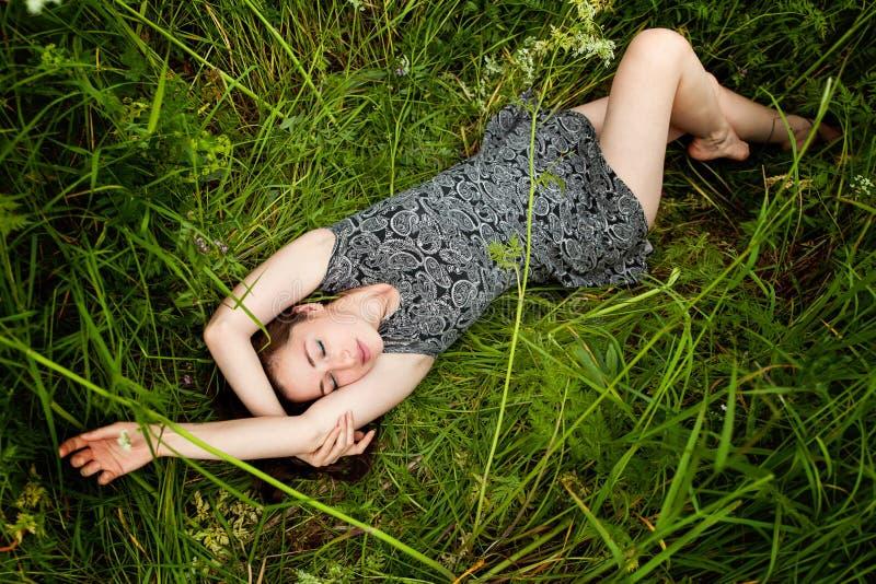Brunettefrau, die auf grünem Gras liegt stockbilder