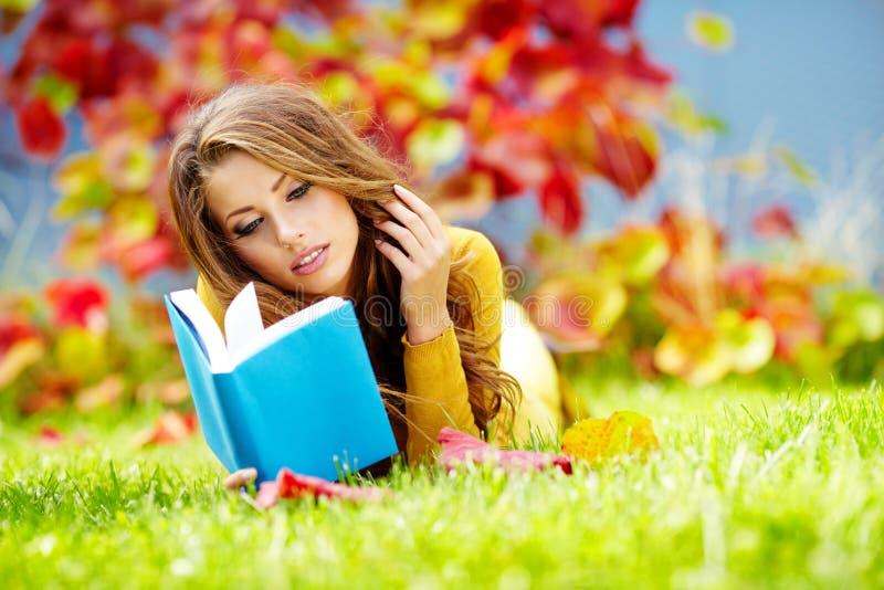 Brunettefrau, die ein Buch liest lizenzfreie stockfotografie