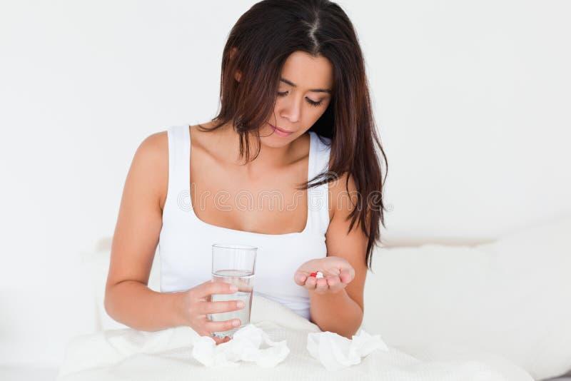 Brunettefrau, die eine Kälte hat, Pillen zu nehmen stockbild