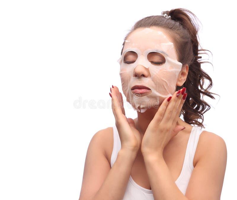 Brunettefrau, die Gesichtsmaskenblatt tut Schönheit und Hautpflegekonzept Mädchen, das Maske an ihrem Gesicht, Atelieraufnahme an lizenzfreies stockfoto