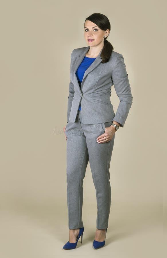 Brunettefrau, die grauen Anzug auf einfachem Hintergrund trägt stockbild