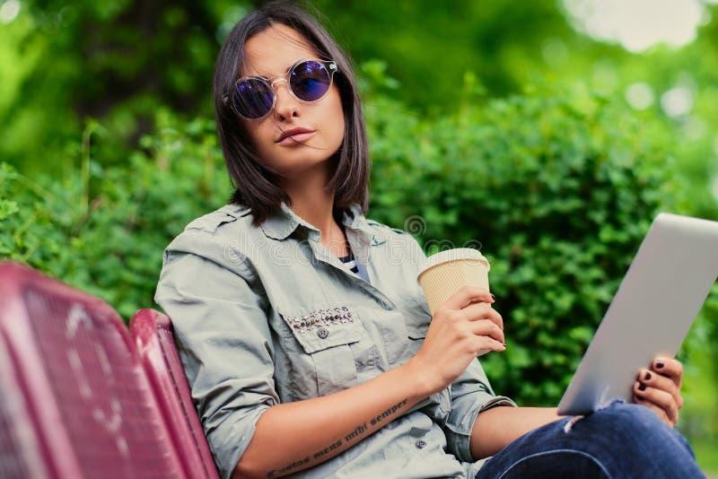 Brunettefrau hält Tablet-PC-Getränkkaffee in einem Sommerpark stockfotos