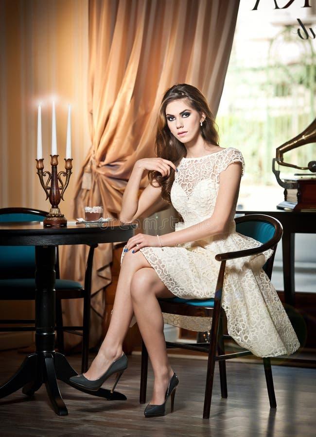 Brunettefrau im eleganten Spitzekleid, das nahe einer Tabelle mit Kerzenständer sitzt stockfotografie
