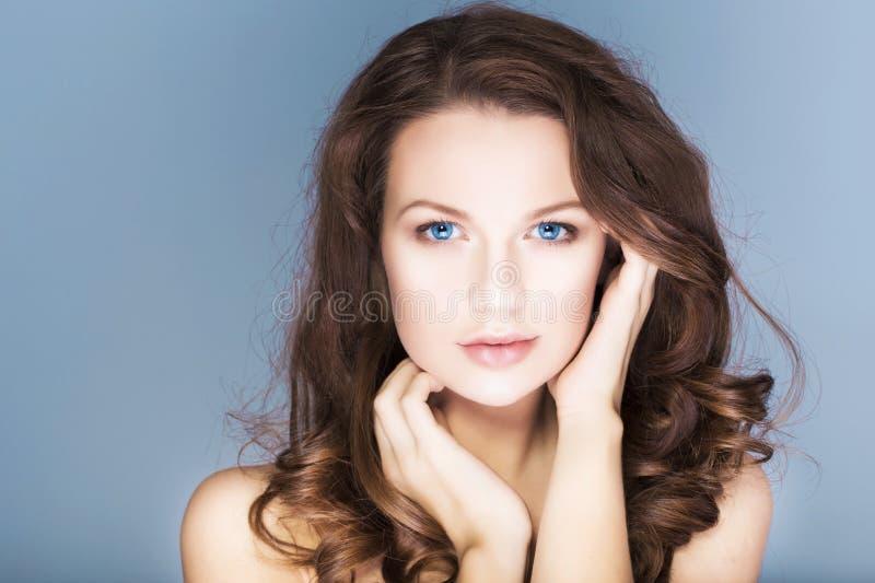Brunettefrau mit blauen Augen außen bilden, natürliche makellose Haut und Hände nahe ihrem Gesicht stockfotos