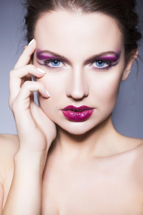 Brunettefrau mit kreativem bilden volle rote Lippen der violetten Lidschatten, blaue Augen und gelocktes Haar mit ihrer Hand auf  stockfotografie