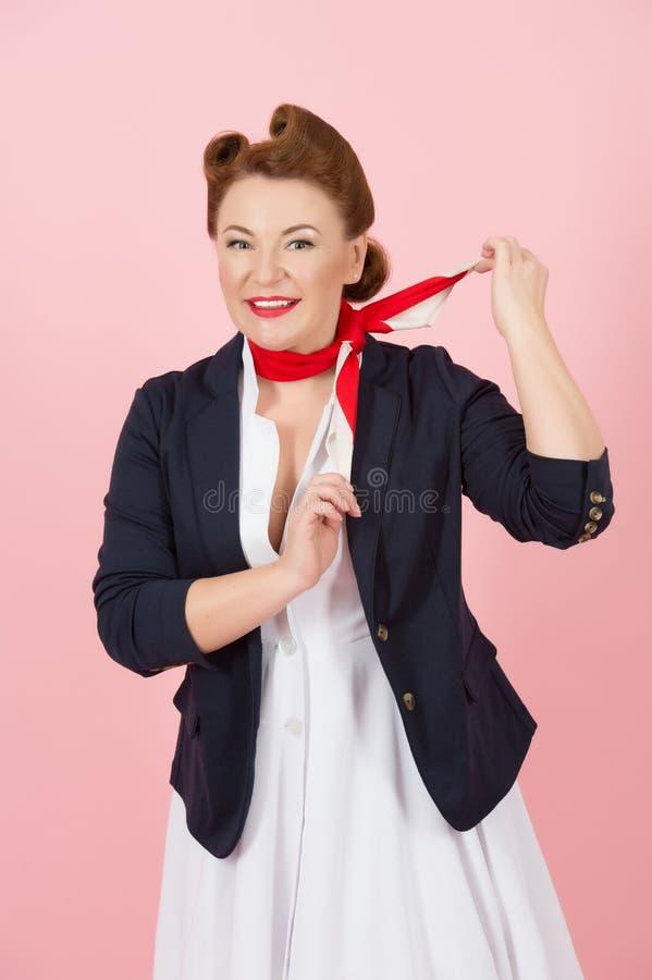 Brunettefrau mit rotem Schal auf Hals Luftuniform für Mädchen auf Flugzeug Lächelndes Mädchen mit Stift-oben reden an und richten stockbild