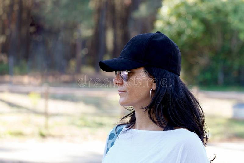 Brunettefrau mit schwarzem Hut im Park stockfotos