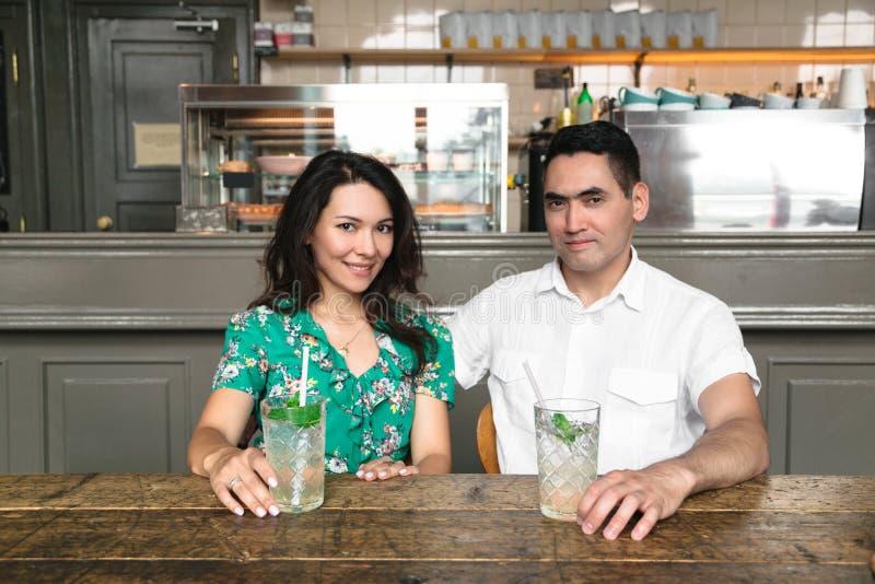 Brunettefrau und -mann, die zusammen sitzen und lächeln lizenzfreie stockbilder