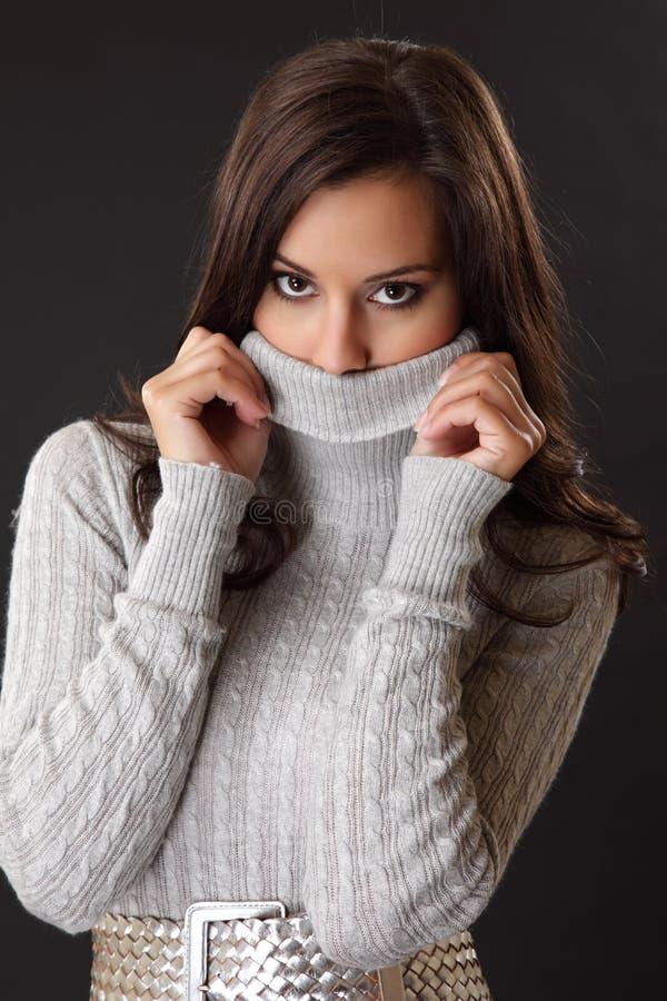 Brunettefrau versteckt ihr halbes Gesicht lizenzfreies stockfoto