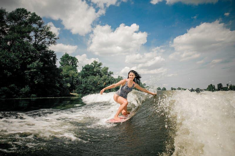 Brunettefrauen-Reiten-wakeboard auf Welle des Motorboots stockfoto