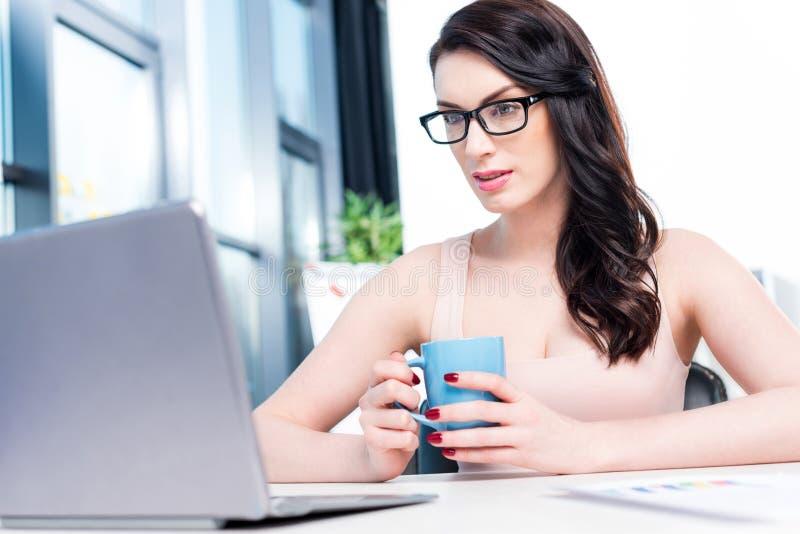 Brunettegeschäftsfrau, die mit Laptop arbeitet und Kaffeetasse im Büro hält lizenzfreie stockfotografie
