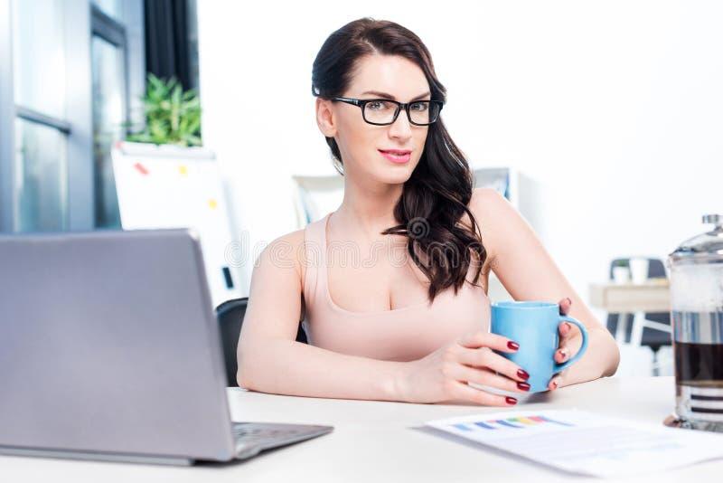 Brunettegeschäftsfrau, die mit Laptop arbeitet und Kaffeetasse im Büro hält stockfoto