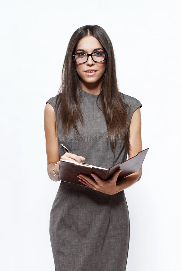 Brunettegeschäftsfrau mit Notizblock stockbild