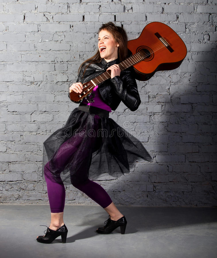 Brunettegitarrenspielerfrau stockfoto