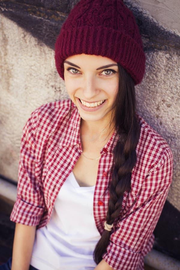 Brunettejugendliche in der Hippie-Ausstattung (kurze Jeanshose, keds, kariertes Hemd, Hut) mit einem Skateboard am Park lizenzfreie stockfotos