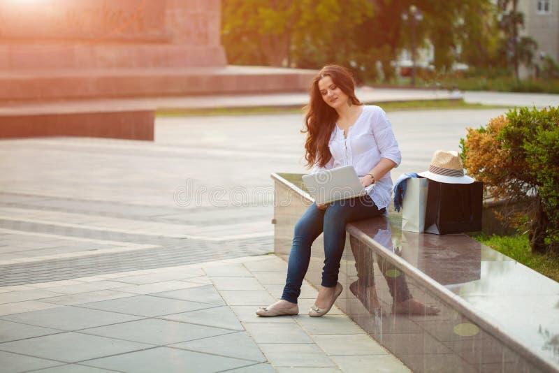 Brunettemädchen, das auf der Straße mit Laptop und dem Einkauf sitzt lizenzfreie stockbilder