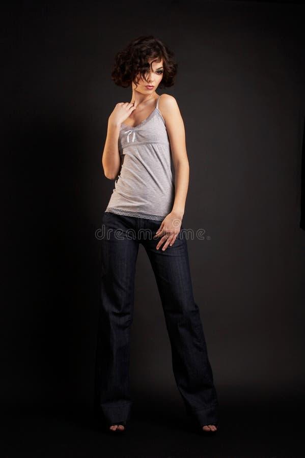 Brunettemädchen, das auf dunklem Hintergrund aufwirft stockfoto
