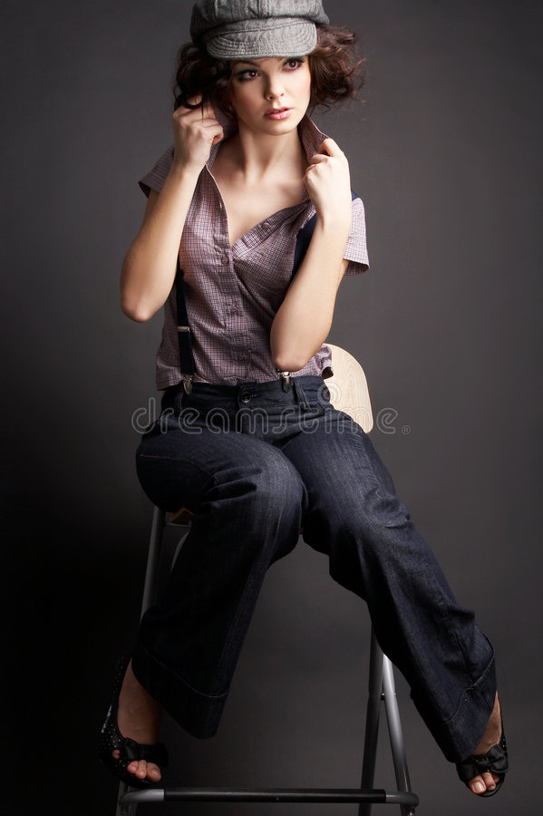 Brunettemädchen, das auf dunklem Hintergrund aufwirft stockfotos