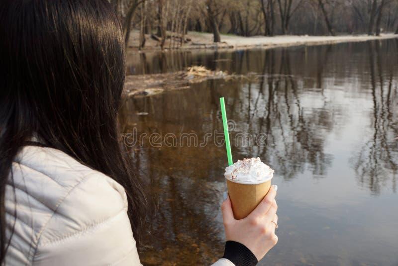 Brunettemädchen, das ein Glas in ihrer Hand mit Kaffee auf dem Wasser nahe dem Wasser hält stockfotografie