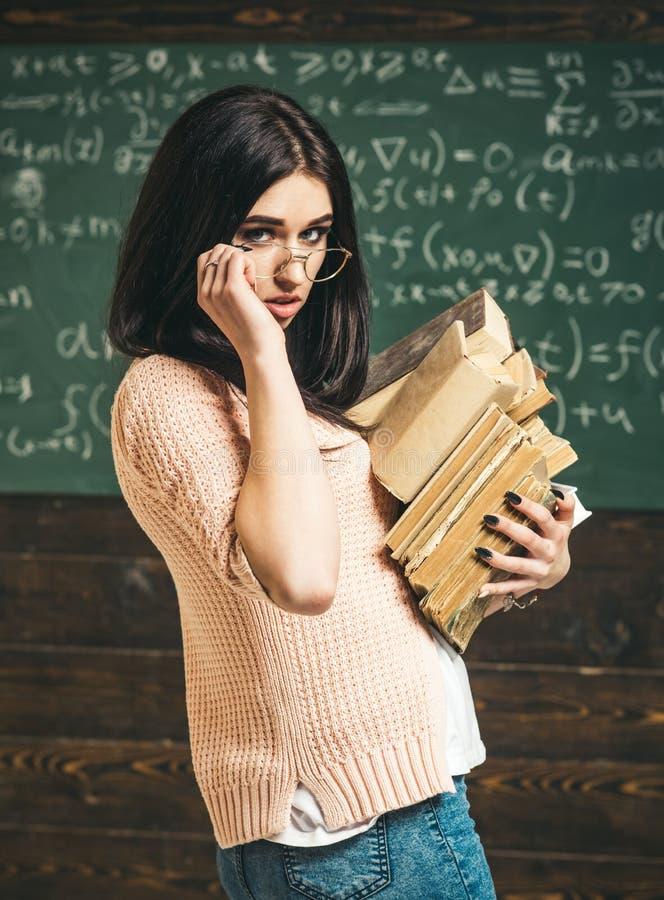 Brunettemädchen in der rosa Wolljacke, die über ihren Gläsern schaut Tragender Stapel der schönen Studentin der Seitenansicht von stockbild