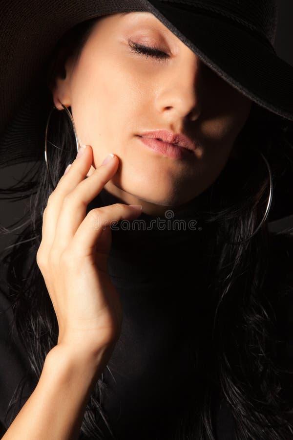 Brunettemädchen im Hut berühren leicht Ihr Gesicht stockfoto